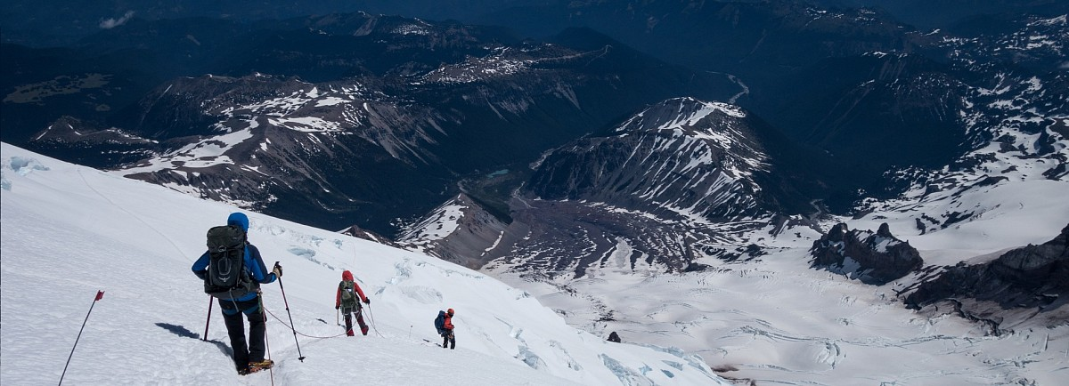 The team descends the glacial east face of Mt. Rainier in Washington State