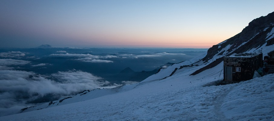Enjoying a serene evening at Camp Muir with Mount St. Helens's ghostly silhouette on the horizon.