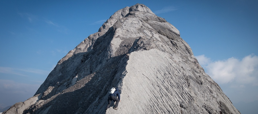 Alex negotiates the intimidating corner slab section of the mountain. The right side of the slab plunges to glacier hundreds of metres below.